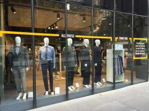 Decal, mannequins and wardrobe on the front window at the Kit store demonstrating the 5 day wardrobe.